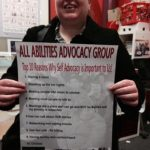 Picture of an All Abilities Advocacy committee member holding up a sign