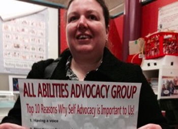 committee member from all Abilities Group holding up sign