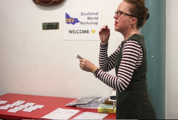 DeafBlind Group committee member signing during a meeting