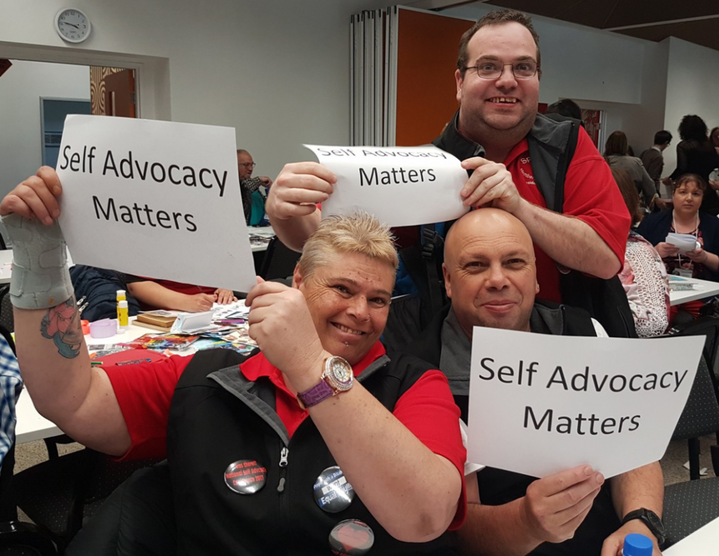 speak out tasmania committee members holding up self advocacy matters signs